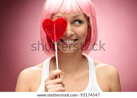 Funny young girl in pink wig holding valentine lollipop and posing for camera across pink background