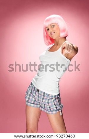 Funny young girl in pink wig posing for camera across pink background - stock photo