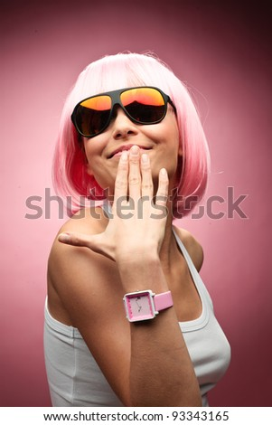 Funny young girl in pink wig posing for camera across pink background