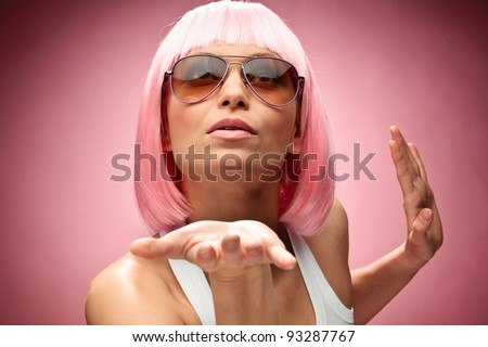 Funny young girl in pink wig showing something for camera across pink background - stock photo