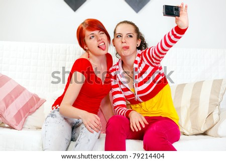 Funny young girlfriends showing  tongues while photographing themselves - stock photo