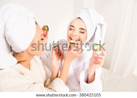 Funny young girls with towels on their heads feeding ech other with slices of cucumber - stock photo