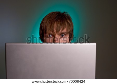 funny young man addicted to his laptop - stock photo