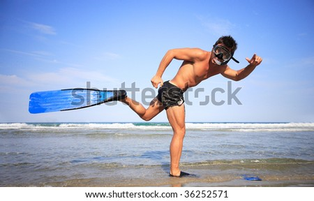 Funny young man ready for fun at sunny beach - stock photo