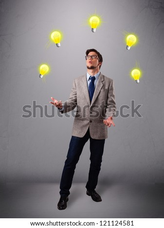 funny young man standing and juggling with light bulbs - stock photo