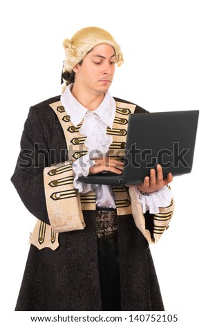 Funny young man wearing medieval costume and posing with a laptop. Isolated on white  - stock photo