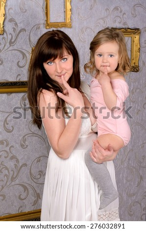 funny young mommy holding her little daughter indoors - stock photo