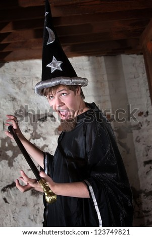 Funny young wizard holding a scepter with eyes rolled up - stock photo