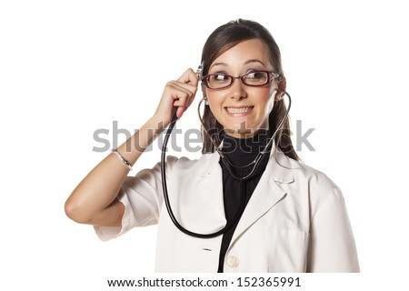 Funny young woman doctor holding a stethoscope to her head and listens to her thought - stock photo