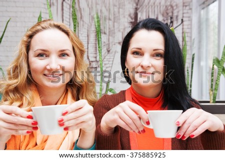 Funny young woman drinking coffee in a cafe