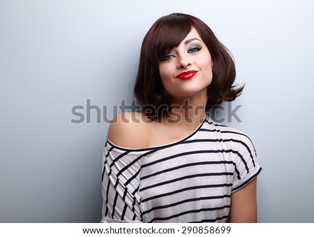 Funny young woman grimacing with short black hair style on black background - stock photo