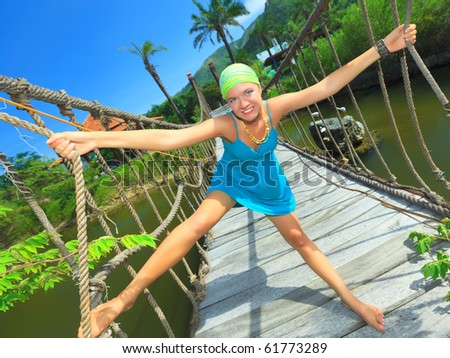 Funny young woman on the suspension bridge