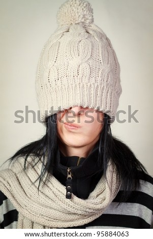 Funny young woman wearing in a winter cap and scarf
