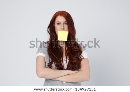 Funny young woman with a post-it note on her mouth. Woman wearing a  blouse with long curly red hair. Uniform light gray background.