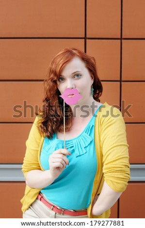 Funny young woman with lips party accessory  - stock photo