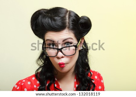 Funny young woman with pin-up make-up and hairstyle posing over yellow background - stock photo