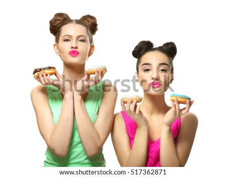 Funny young women with tasty donuts on white background