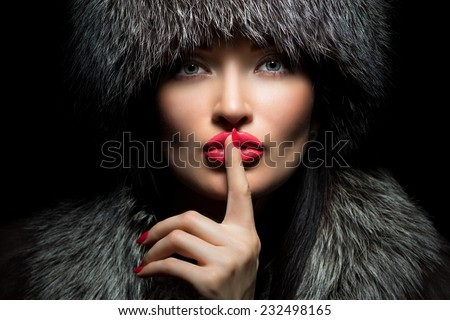 Fur Fashion. Beautiful Girl with red lips and manicure in Fur Hat. Winter Woman Portrait - stock photo