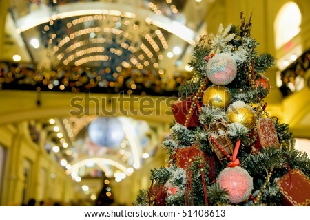 Fur-tree densely covered by Christmas ornaments in shopping centre - stock photo