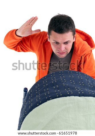 furious, angry, bad father with raised hands and baby buggy - stock photo