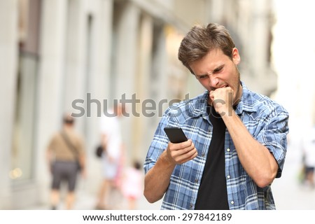 furious angry man watching apps in the mobile phone in the street - stock photo