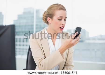 Furious attractive businesswoman on the phone in bright office - stock photo