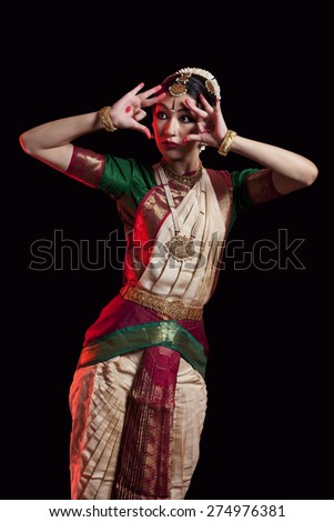 Furious Bharatanatyam dancer performing over black background