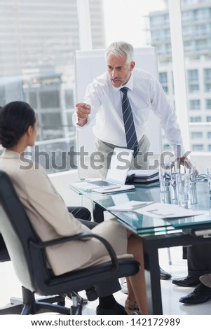 Furious boss pointing at an employee during a meeting - stock photo