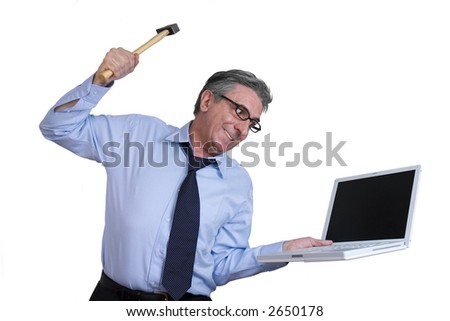 Furious businessman destroying his laptop with a hammer. - stock photo