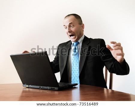 furious businessman looking at his laptop - stock photo