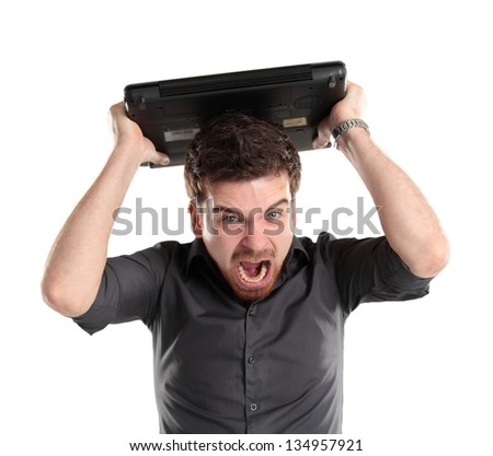 Furious businessman looking at his laptop and shouting