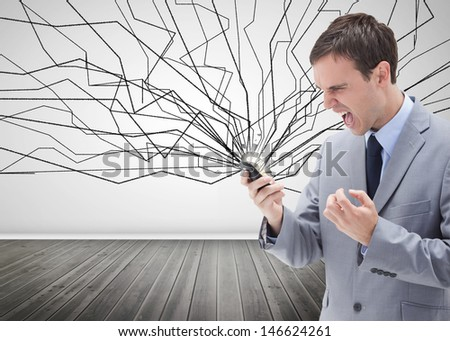 Furious businessman looking at his mobile phone in a room - stock photo