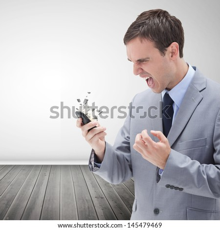 Furious businessman screaming and looking at his mobile phone causing it to break - stock photo