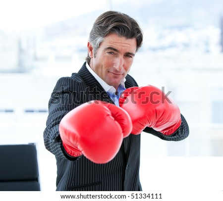 Furious businessman wearing boxing gloves in his office - stock photo