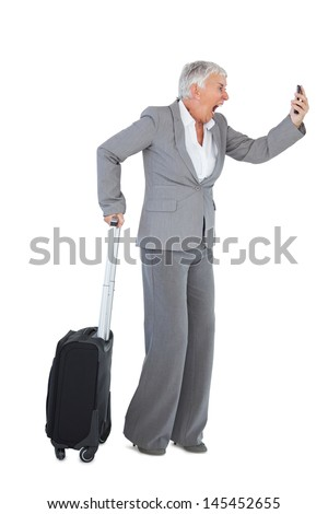 Furious businesswoman screaming during a call with suitcase on white background - stock photo