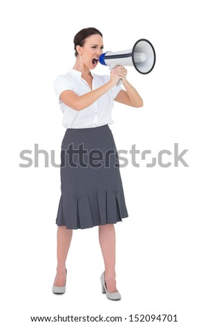 Furious businesswoman shouting in her megaphone while posing on white background