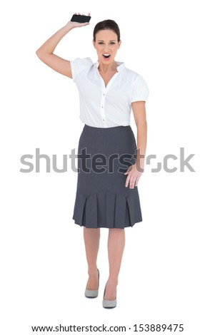 Furious businesswoman throwing her phone away while posing on white background - stock photo