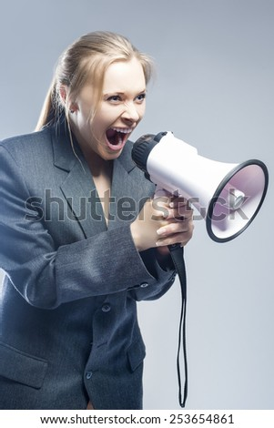 Furious Caucasian Blond Female in Suite Shouting Using Megaphone. Against Gray Background. Vertical Image - stock photo
