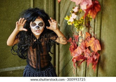 Furious girl in wig and Halloween attire - stock photo