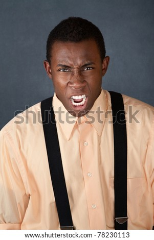Furious handsome young African-American male with suspenders - stock photo