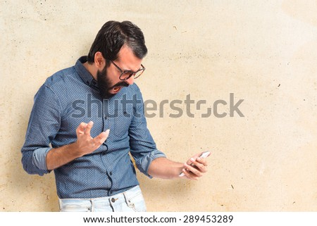 Furious hipster man talking to mobile - stock photo