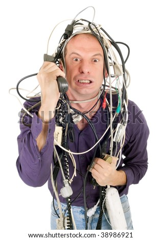 furious man tangled with electric cables phoning technology support - stock photo