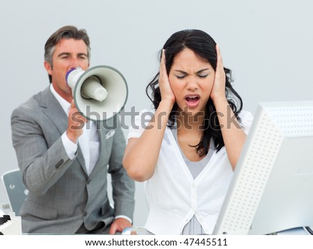 Furious manager shouting through a megaphone in a colleague's ears in the office - stock photo