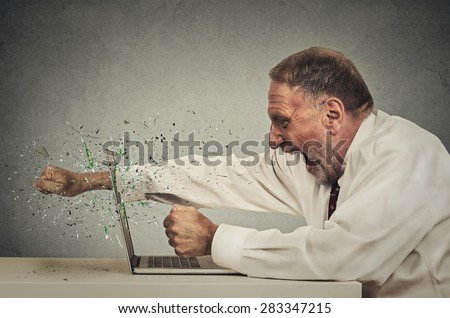 furious senior businessman throws punch into computer screaming isolated grey office wall background. Negative human emotions, facial expressions, feelings, aggression, anger management issues concept - stock photo