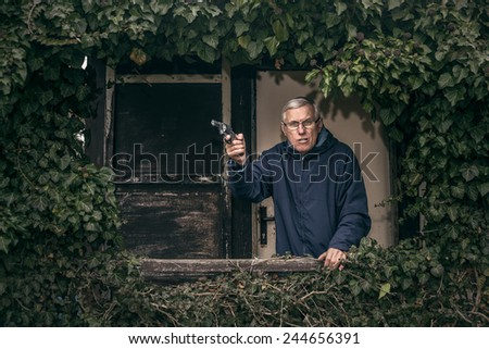Furious senior man gesturing with a gun protecting his property, standing in front of old overgrown cabin. - stock photo