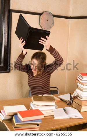 Furious Student girl with books and laptop in her room - stock photo