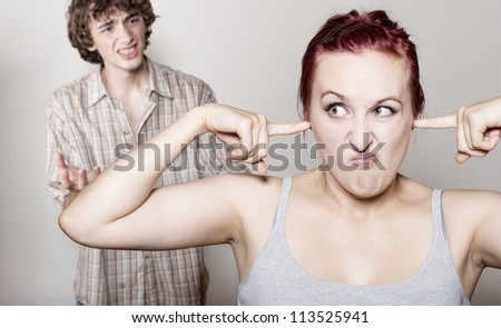 Furious, the husband yells at his wife. Focus on woman - stock photo