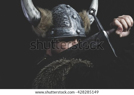 Furious, Viking warrior with iron sword and helmet with horns - stock photo