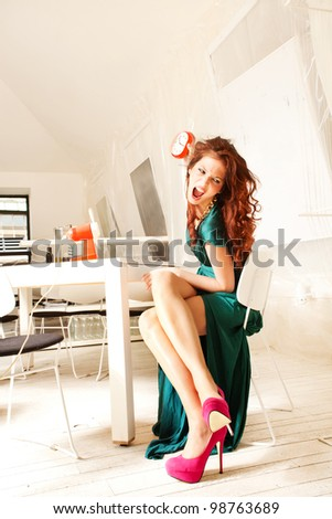 furious woman throw clock, sit in white modern room - stock photo