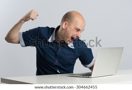 Furious young businessman about to punch his laptop - stock photo